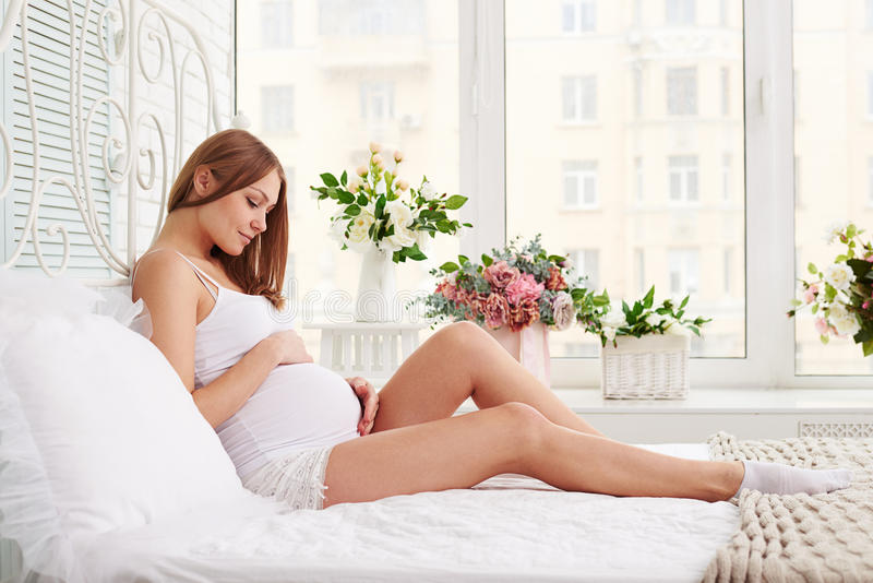 Femme enceinte s'asseyant sur le lit et touchant son ventre appréciant le Th image libre de droits