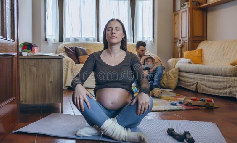 Femme enceinte s'exerçant dans le salon photographie stock