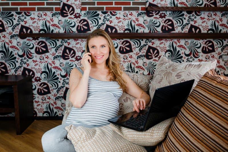 Femme enceinte se reposant sur le sofa, parlant au téléphone et travaillant sur l'ordinateur portable photographie stock
