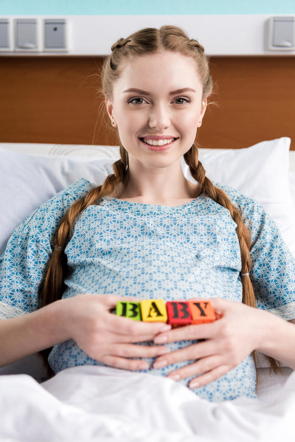Femme enceinte se situant dans le lit d'hôpital et tenant les cubes colorés avec le bébé de mot photos libres de droits
