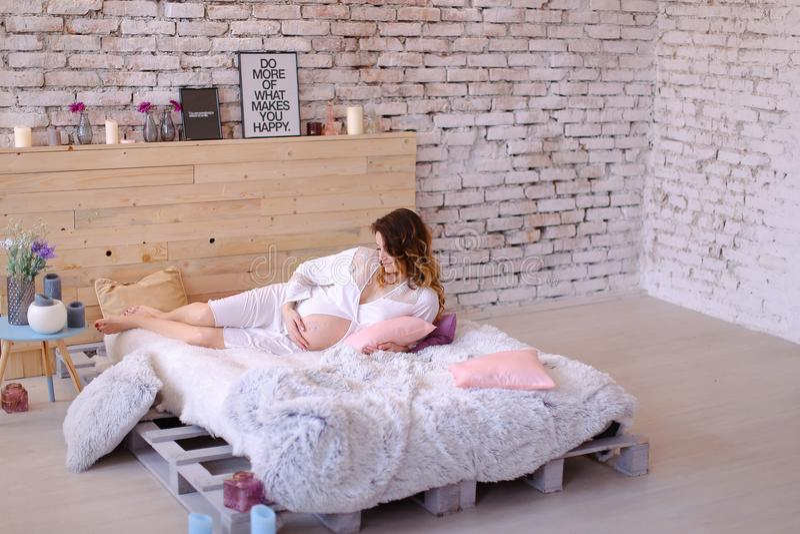 Femme enceinte se tenant dans la robe blanche, le mur en bois et des lampes à l'arrière-plan photos stock
