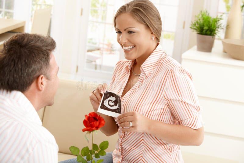 Femme enceinte souriant à l'homme photo stock
