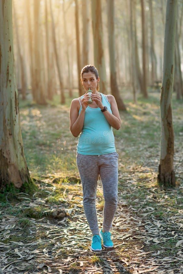 Femme enceinte sportive sur la séance d'entraînement extérieure de forme physique avec le smoothie de detox photo stock