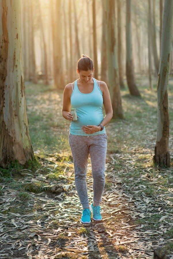 Femme enceinte sportive sur la séance d'entraînement extérieure de forme physique avec le smoothie de detox images stock