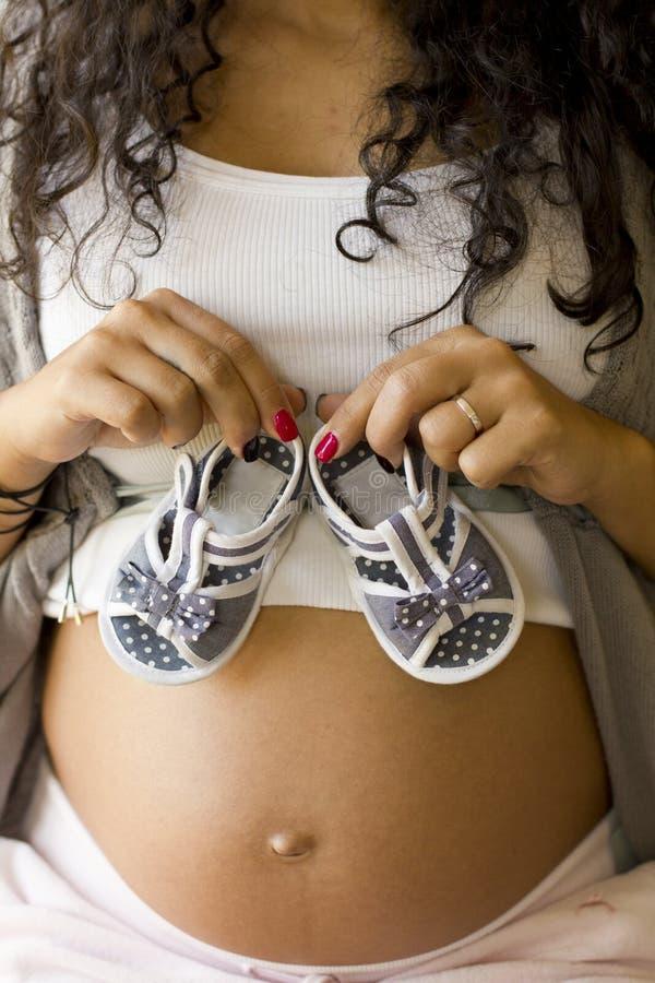 Femme enceinte tenant des chaussures de bébé images stock