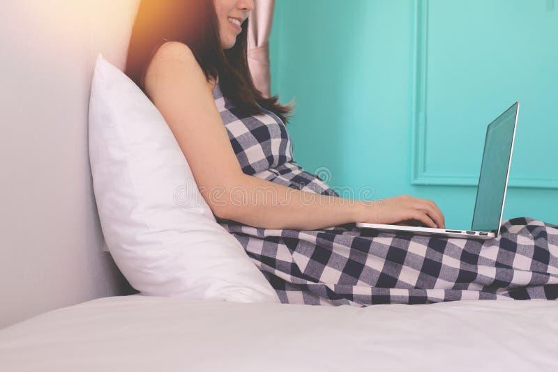 Femme enceinte utilisant l'ordinateur portable sur le lit blanc dans la chambre à coucher, concept des données de découverte images stock
