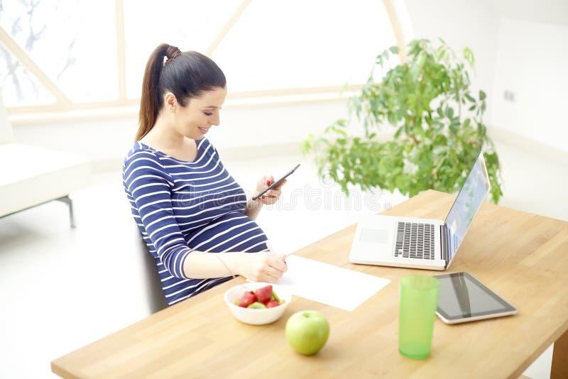 Femme enceinte utilisant le téléphone portable et l'ordinateur portable photos libres de droits