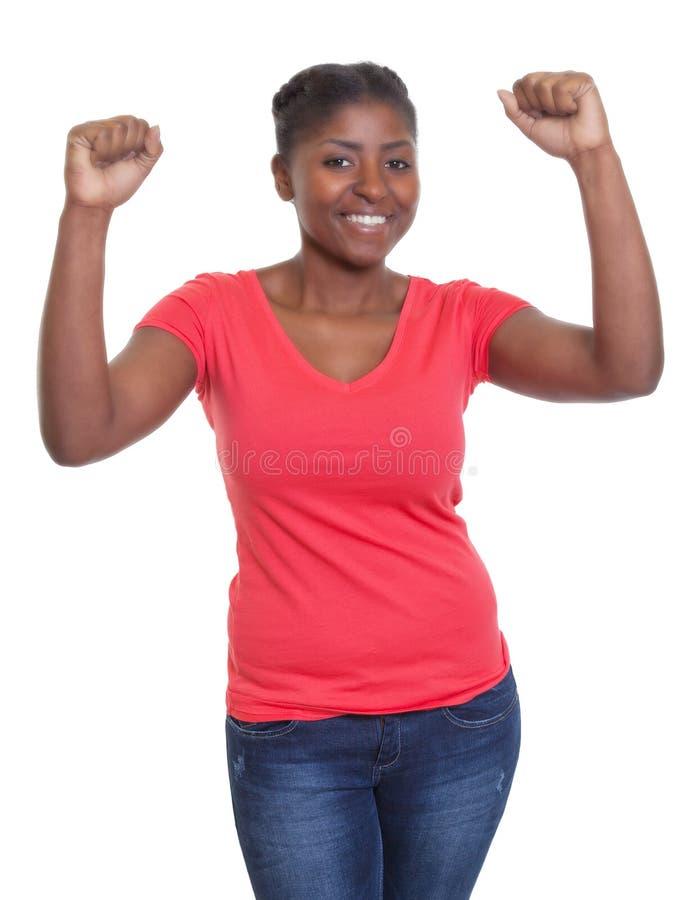 Femme encourageante d'afro-américain dans une chemise rouge et des jeans photos stock