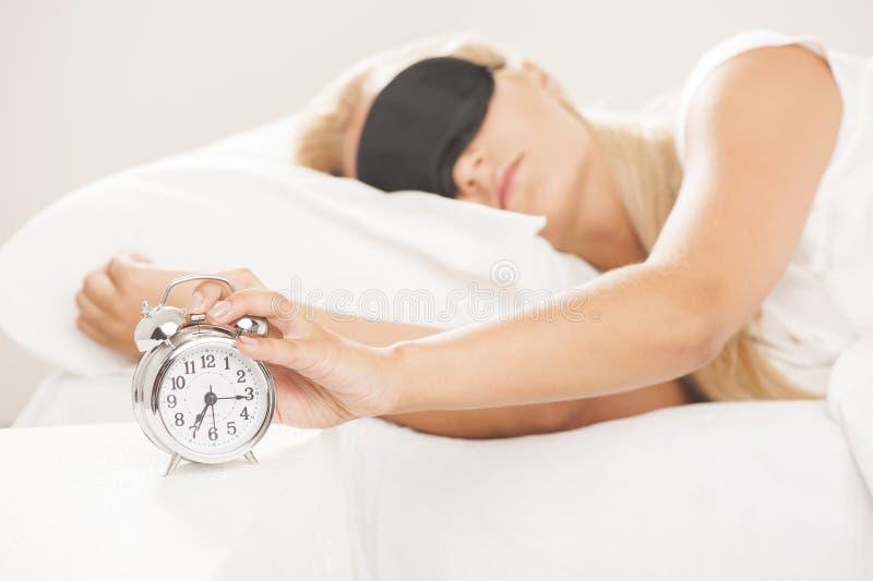 Femme endormie dans le lit tandis que son alarme montre le temps tôt à la maison dans la chambre à coucher réveil et femme noirs  images stock