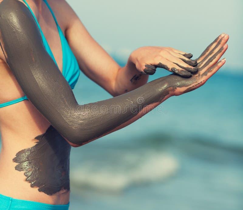 Femme enduisant le masque de boue sur le corps photos stock