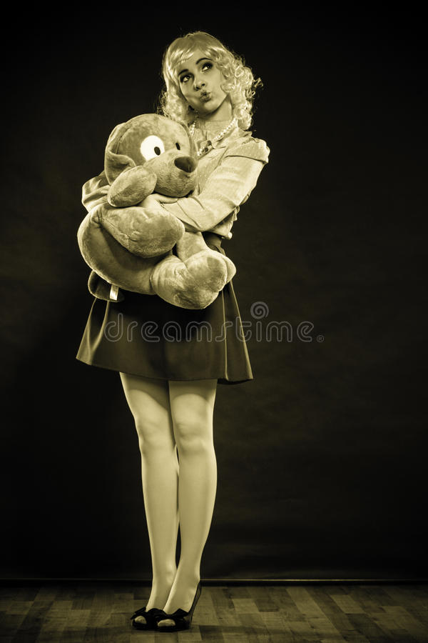 Femme enfantine avec le jouet de chien sur le noir photographie stock