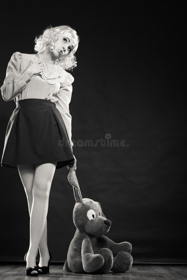 Femme enfantine avec le jouet de chien sur le noir photos libres de droits