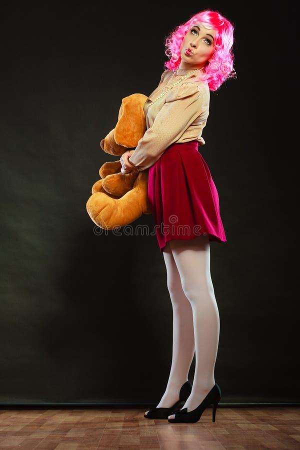 Femme enfantine avec le jouet de chien sur le noir images libres de droits