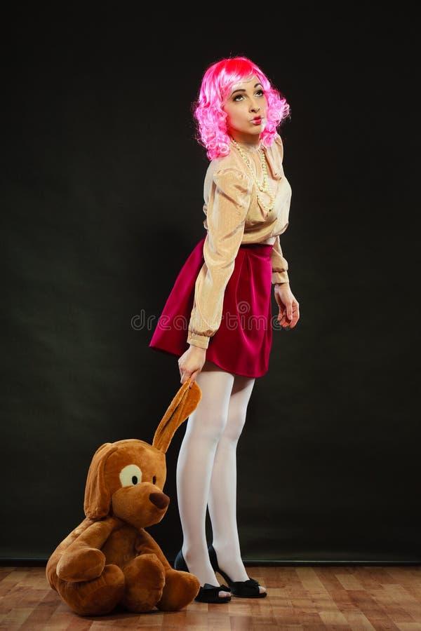 Femme enfantine avec le jouet de chien sur le noir photo libre de droits