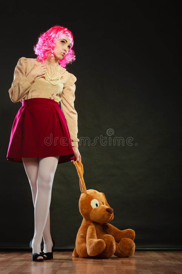 Femme enfantine avec le jouet de chien sur le noir image stock