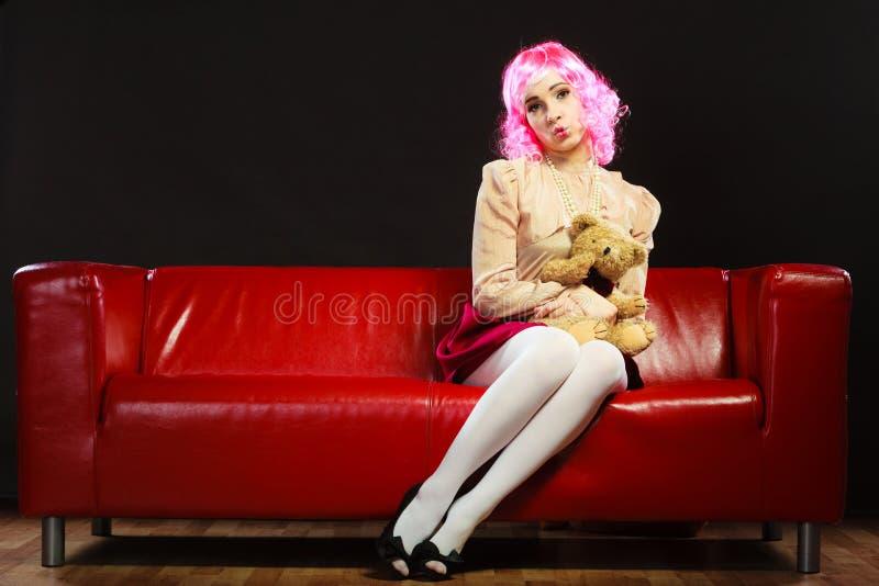 Femme enfantine et ours de nounours se reposant sur le divan photos stock