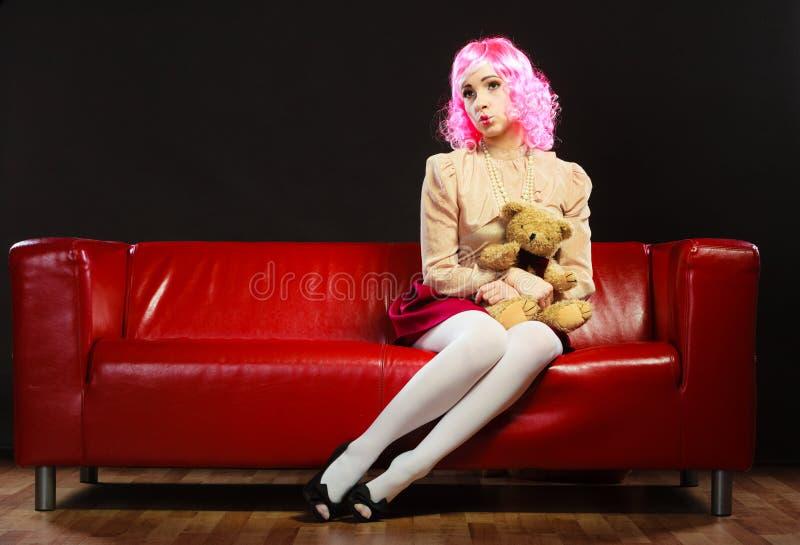 Femme enfantine et ours de nounours se reposant sur le divan images stock