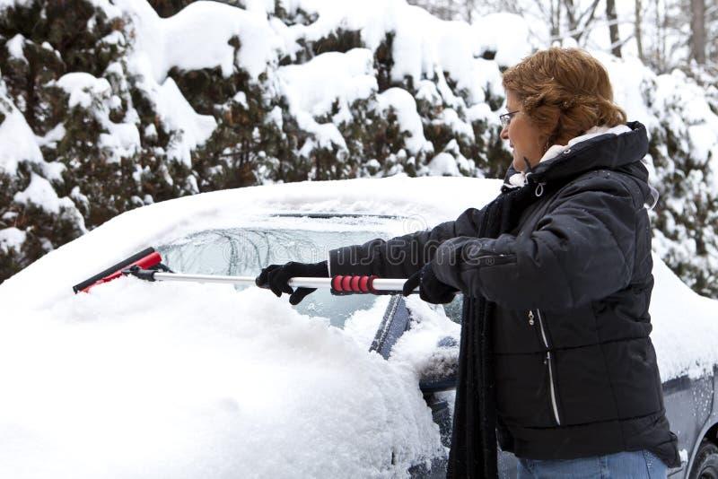 Femme enlevant la neige de son véhicule photos stock