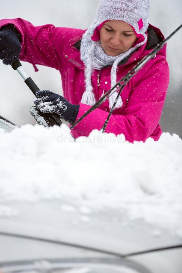 Femme enlevant la neige de son véhicule photographie stock