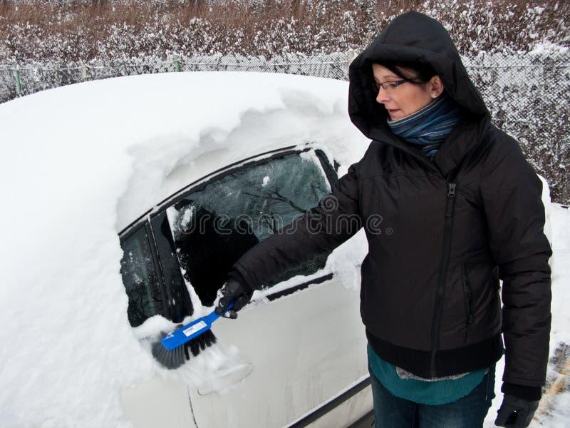 Femme enlevant la neige du véhicule photos stock