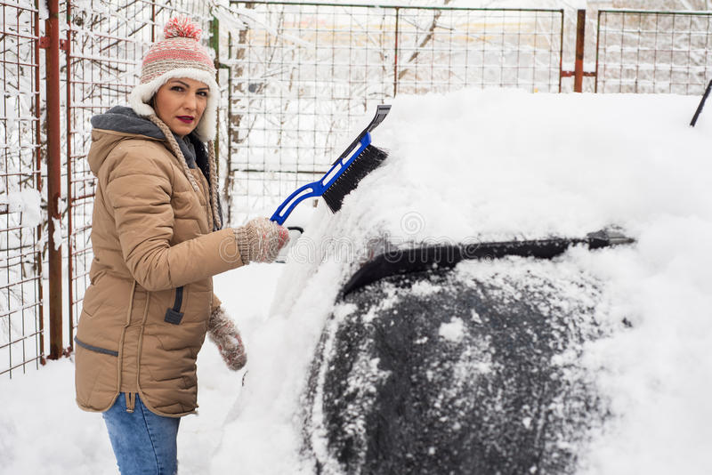Femme enlevant la neige du véhicule photo libre de droits