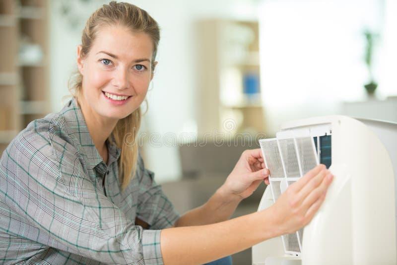 Femme enlevant le filtre d'appareils photographie stock