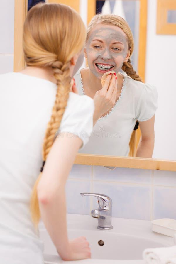 Femme enlevant le masque facial de boue avec l'éponge image stock