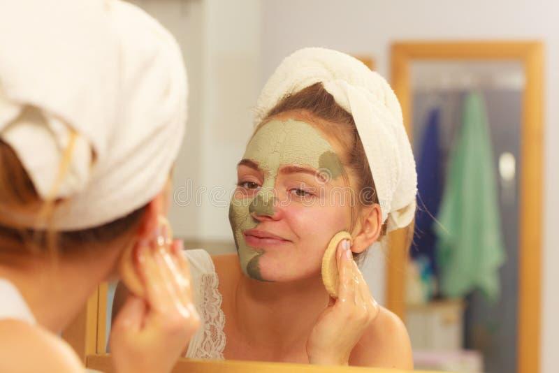 Femme enlevant le masque facial de boue d'argile dans la salle de bains images libres de droits