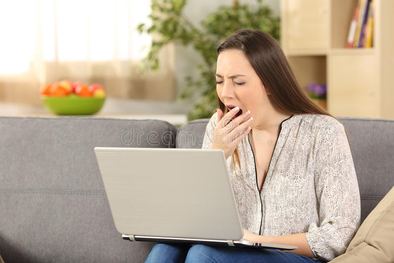Femme ennuyée sur la ligne baîllant à la maison photo libre de droits