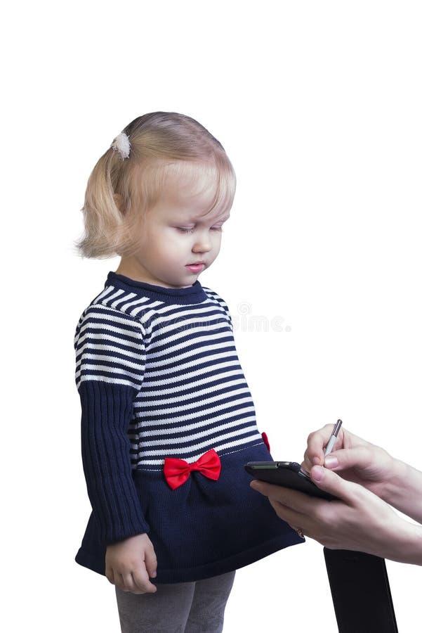 Femme enseignant à petite fille la blonde sur un stylet de smartphone à photographie stock
