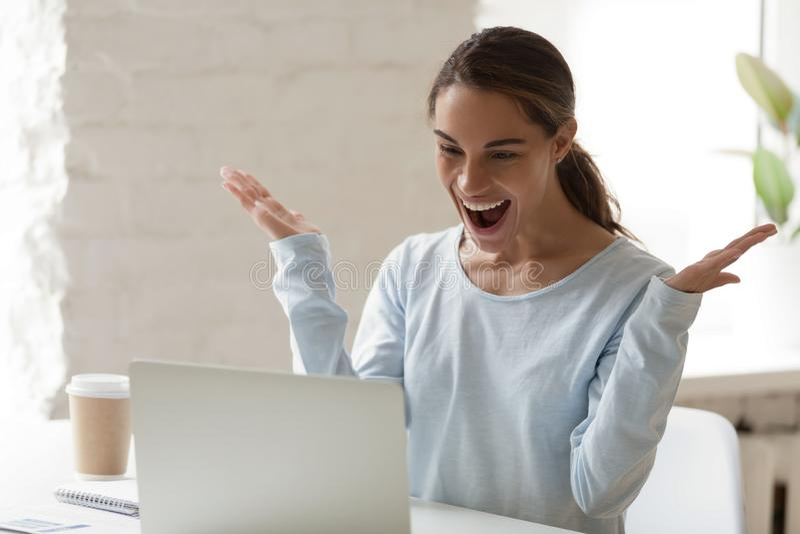 Femme enthousiaste à l'aide de l'ordinateur portable, célébrant la réception de bonnes nouvelles photographie stock