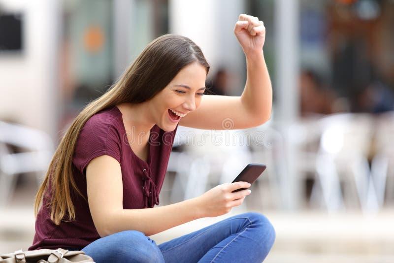 Femme enthousiaste avec un téléphone dans la rue photo libre de droits