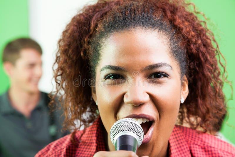 Femme enthousiaste chantant dans le studio d'enregistrement image libre de droits