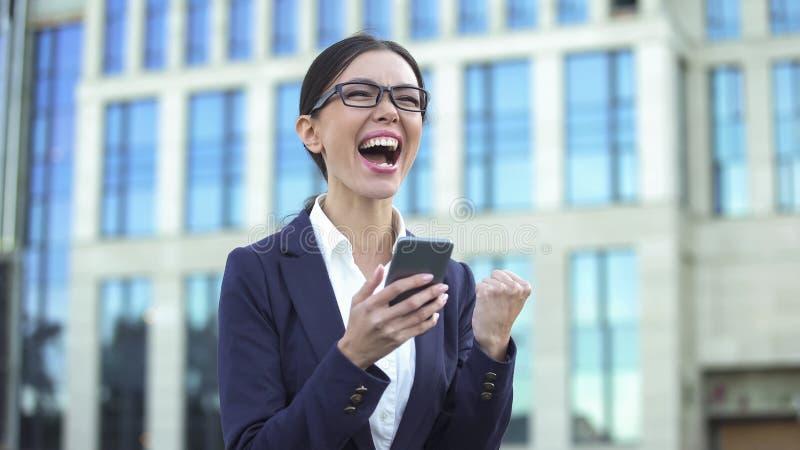 Femme enthousiaste d'affaires montrant le geste de succès lisant l'email mobile, carrière photo libre de droits