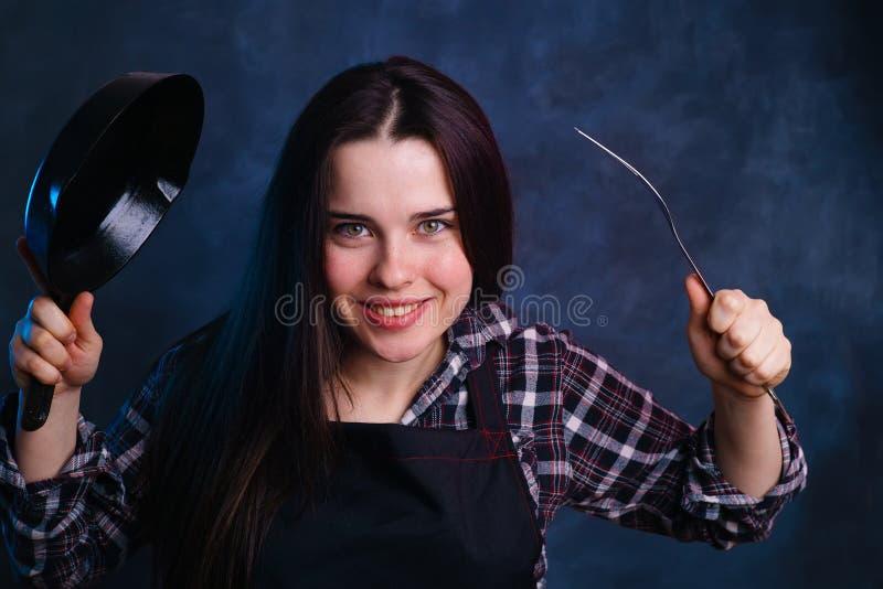 Femme enthousiaste de jeune femme au foyer attirante avec la poêle photo stock