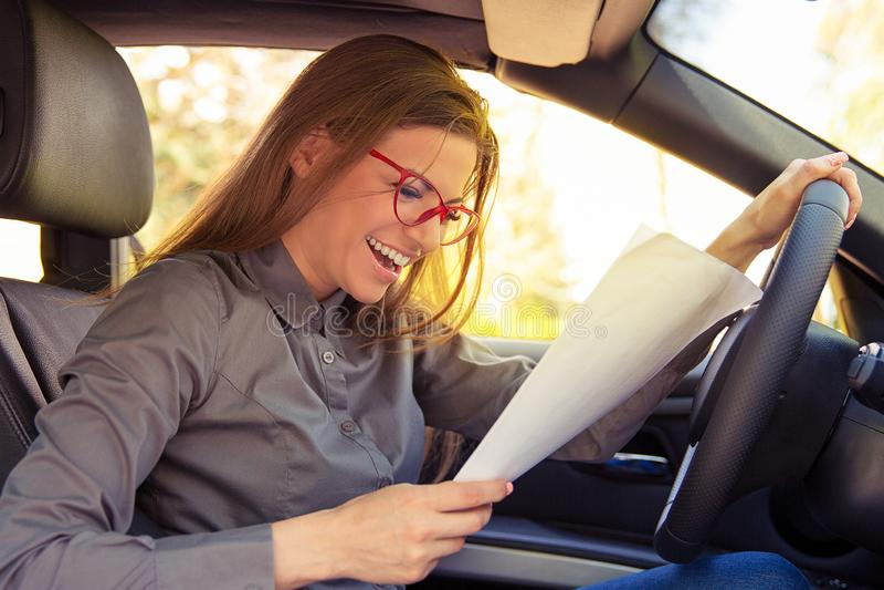Femme enthousiaste en journal de lecture de voiture images libres de droits