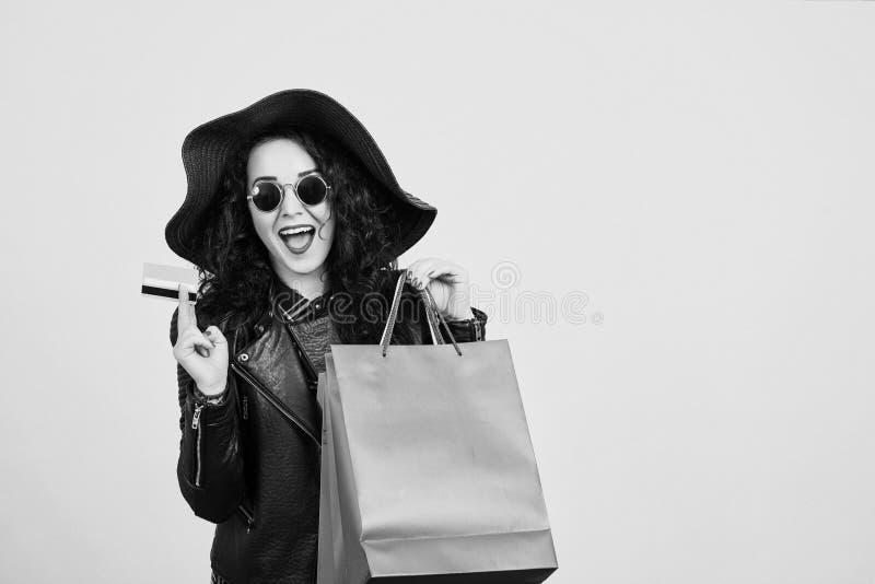 Femme enthousiaste heureuse de hippie dans des lunettes de soleil tenant la carte de crédit et les sacs à provisions colorés ? fe images stock