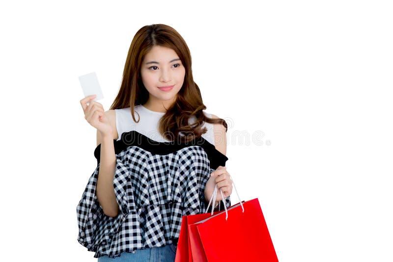 Femme enthousiaste heureuse tenant et tenant les paniers et le point colorés de doigt quelque chose d'isolement photographie stock