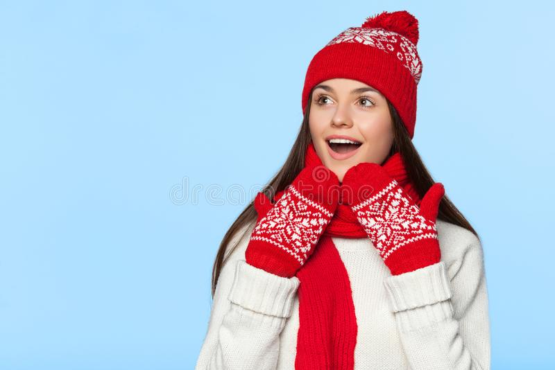 Femme enthousiaste regardant en longueur dans l'excitation Fille étonnée de Noël utilisant le chapeau tricoté et l'écharpe chauds photos stock