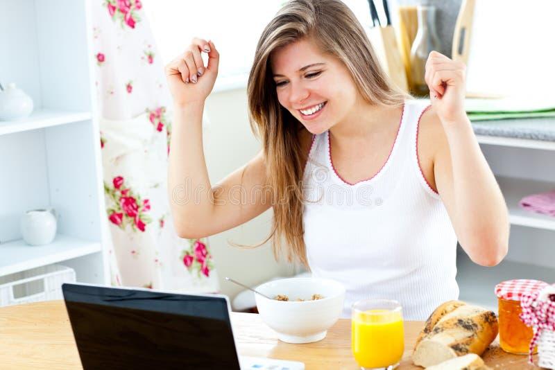 Femme enthousiaste regardant son ordinateur portatif avec des bras vers le haut photographie stock