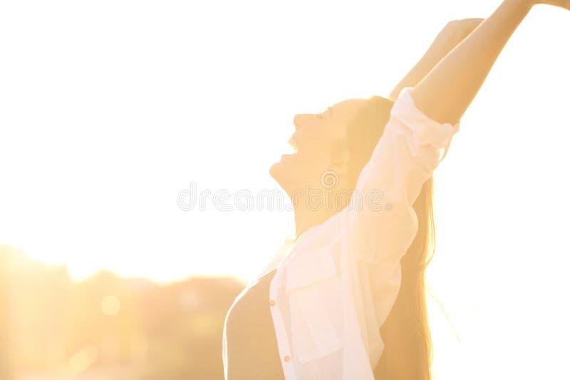 Femme enthousiaste soulevant des bras au coucher du soleil images stock