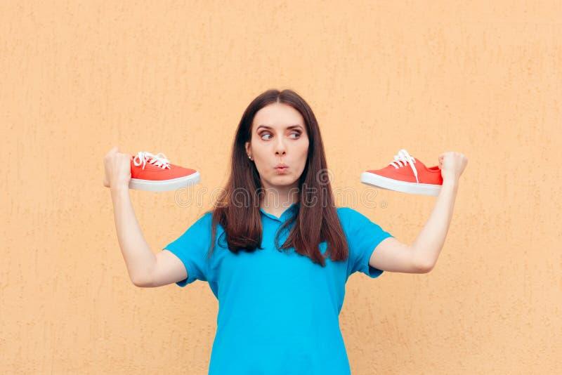 Femme enthousiaste tenant une paire de chaussures rouges de sport image stock