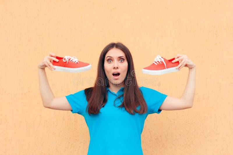 Femme enthousiaste tenant une paire de chaussures rouges de sport photos libres de droits