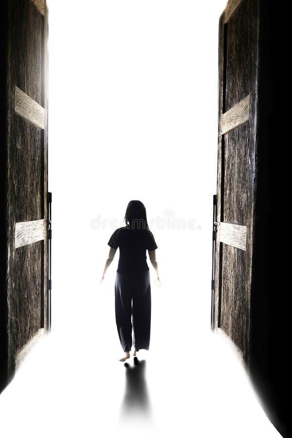 Femme entrant dans la lumière par la grande porte ouverte photos stock