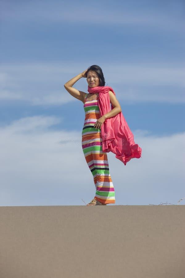 Femme enveloppée en tissu rose sur le sable photo stock
