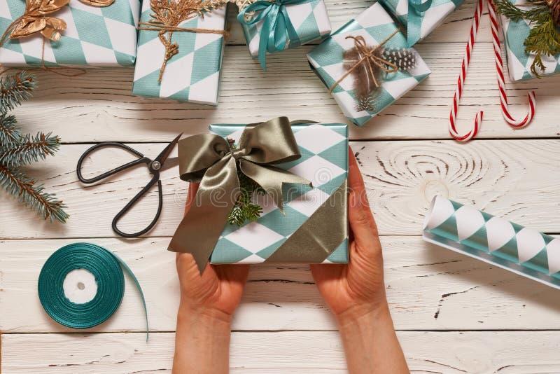 Femme enveloppant des cadeaux de Noël au-dessus de fond en bois photographie stock