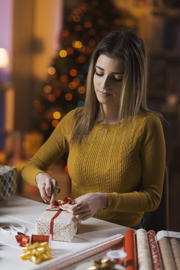 Femme enveloppant des cadeaux de No?l ? la maison images stock