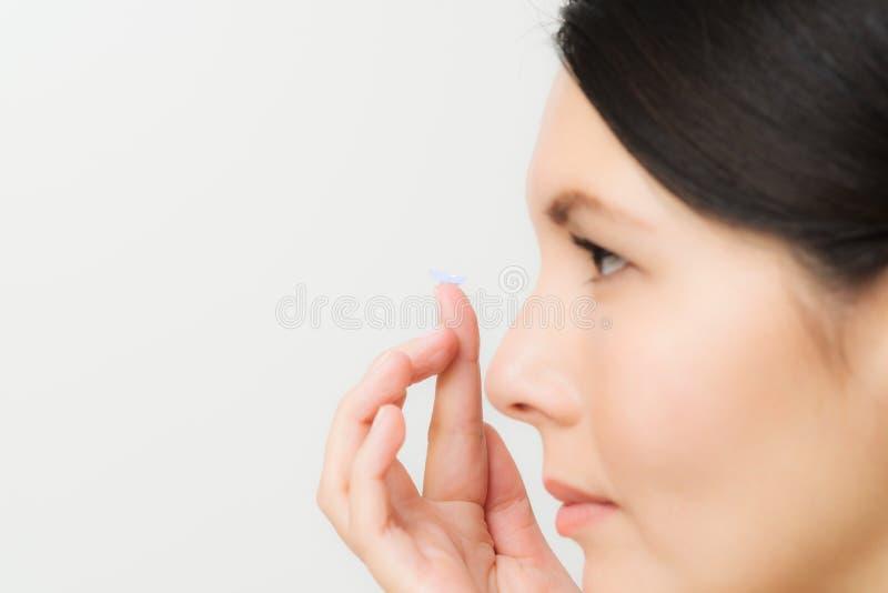 Femme environ pour placer un verre de contact dans son oeil photographie stock