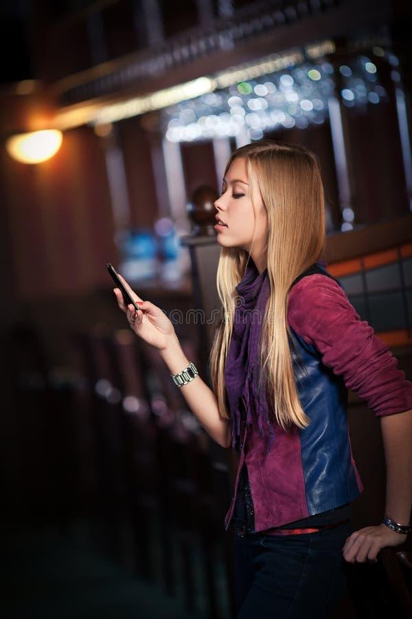 Femme envoyant des sms sur le smartphone dans le bar photo stock