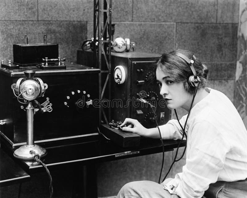 Femme envoyant le code Morse utilisant le télégraphe (toutes les personnes représentées ne sont pas plus long vivantes et aucun d image libre de droits